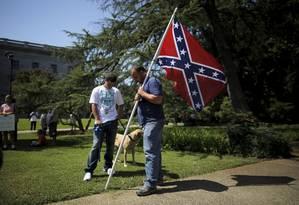 Homem carrega a bandeira confederada diante do Capitólio da Carolina do Sul Foto: BRIAN SNYDER / REUTERS