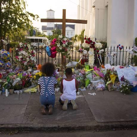 Duas crianças rezam perto de centenas de flores e cartões do lado de fora da Igreja Episcopal Emanuel, cenário do massacre que deixou nove mortos Foto: JIM WATSON / AFP
