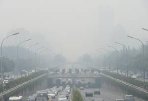 Veículos transitam por Pequim com poluição do ar visível Foto: STR / AFP