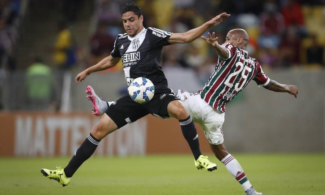 Wellington Silva, do Fluminense, divide a bola com um jogador da Ponte Preta Guito Moreto / Agência O Globo