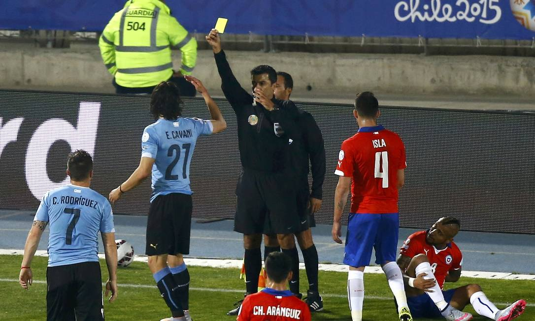 Cavani reclama com o bandeirinha e leva o cartão amarelo do brasileiro Sandro Meira Ricci RICARDO MORAES / REUTERS