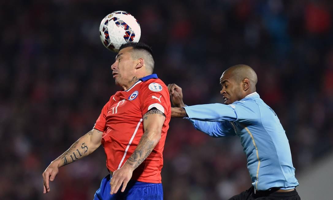 O uruguaio Sánchez disputa a bola com Medel RODRIGO ARANGUA / AFP