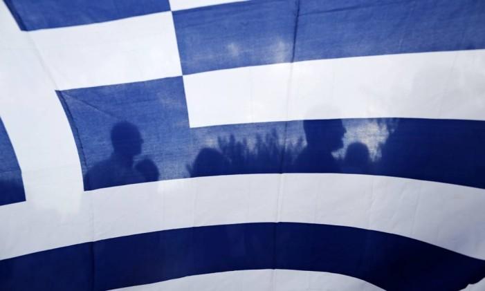 Manifestantes passam por trás de bandeira grega Foto: Konstantinos Tsakalidis / Bloomberg News/22-6-2015