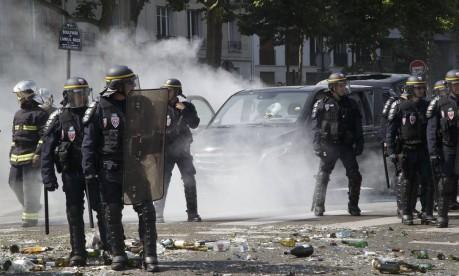 Confronto. Policiais ao lado de carro queimado por taxistas: protesto em Paris contra a entrada do serviço UberPOP Foto: Michel Euler 25/06/2015 / AP