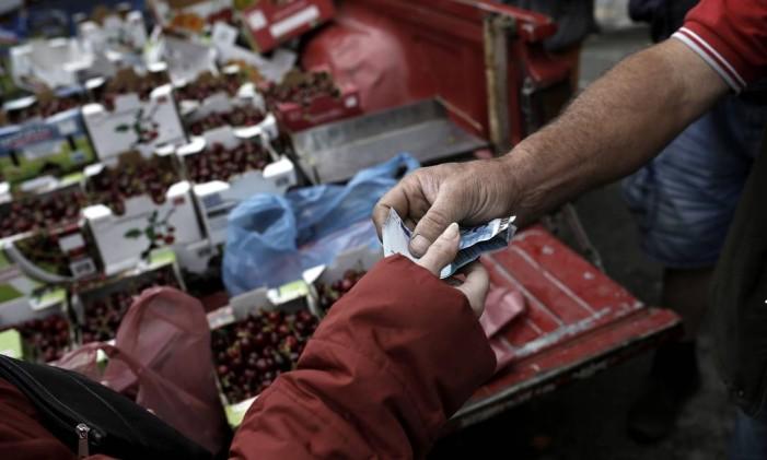Cliente faz compra no mercado da rua Kassandrou, em Tesalônica, na Grécia Foto: Konstantinos Tsakalidis / Bloomberg News/28-5-2015