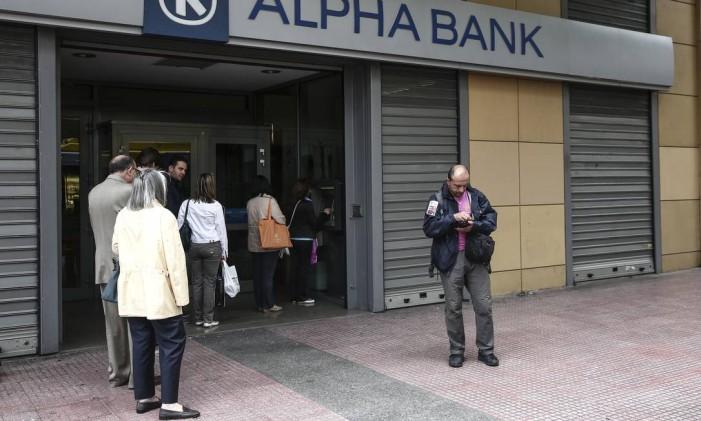 Clientes fazem fila para sacar no caixa eletrônico do Alpha Bank Foto: Yorgos Karahalis / Bloomberg News/29-5-2015