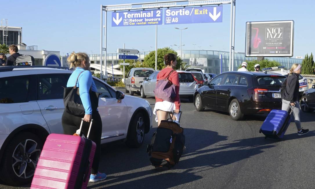 Passageiros tiveram que carregar suas malas pela via que leva aos terminais do aeroporto de Nice por causa do bloqueio dos taxistas Foto: JEAN-PIERRE AMET / REUTERS