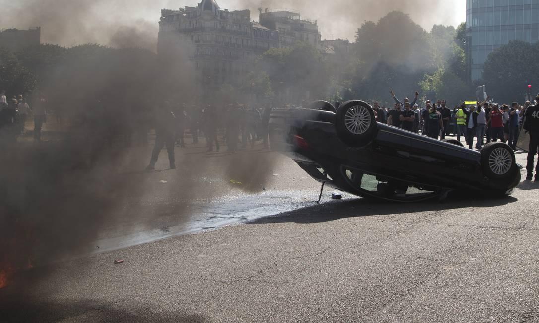 Um carro foi virado e queimado Foto: Michel Euler / AP