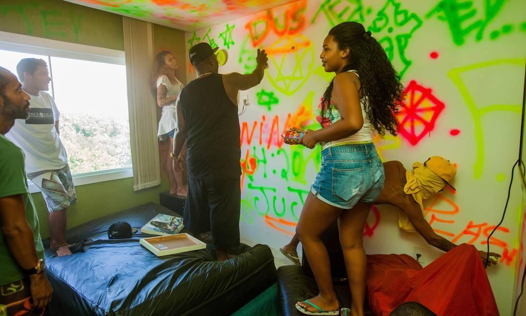 Mr. Catra ajuda seus filhos na pintura da parede de um dos quartos com spray Foto: Bárbara Lopes / Agência O Globo