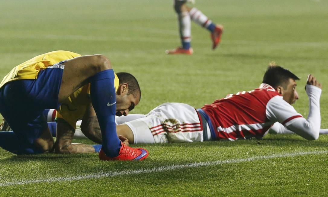 Dani Alves e o paraguaio Edgar Benitez caem no gramado em Concepción MARIANA BAZO / REUTERS