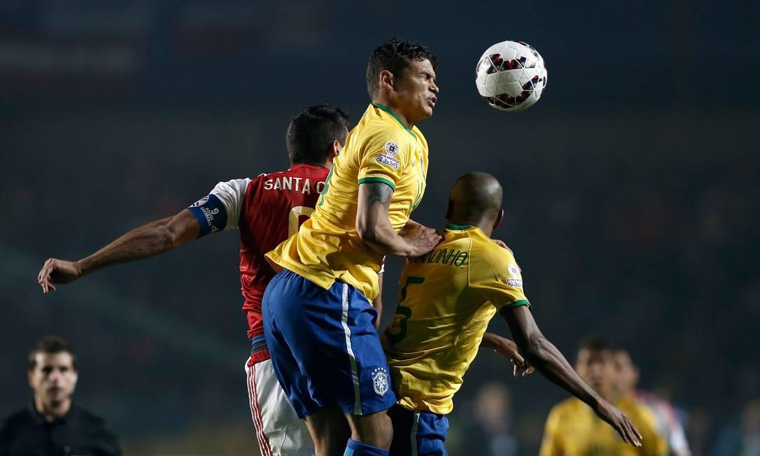 Thiago Silva e Fernandinho disipuam a bola com Roque Santa Cruz Silvia Izquierdo / AP