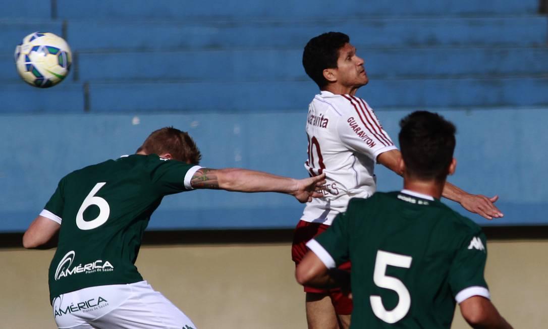 Magno Alves disputa a bola com dois zagueiros do Goiás Nelson Perez / Fluminense