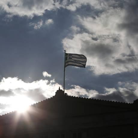 Bandeira da Grécia no topo do Parlamento, em Atenas Foto: Angelos Tzortzinis/AFP
