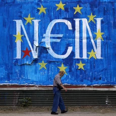 Homem caminha em frente a cartaz anti-União Europeia Foto: ALKIS KONSTANTINIDIS / REUTERS