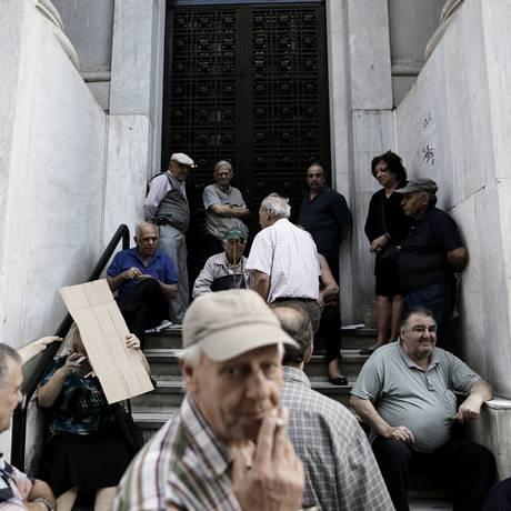 Pensionistas gregos esperam o pagamento em frente ao Banco Nacional da Grécia Foto: Konstantinos Tsakalidis / Bloomberg News