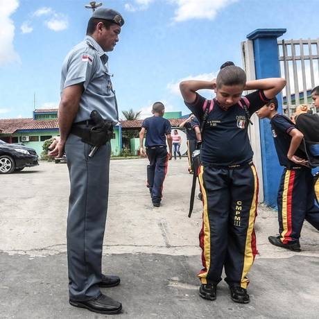 O PM Idevandro Ricardo Colares observa a entrada e inspeciona o uniforme dos alunos Foto: ANDRE COELHO / Agência O Globo