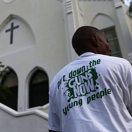 """Homem usa camisa com dizeres """"abaixem as armas agora, jovens"""", em frente a igreja onde o atirador Dylann Roof matou nove pessoas em Charleston, na Carolina do Sul Foto: JOE RAEDLE / AFP"""