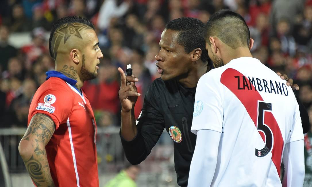 O árbitro Jose Argote conversa com o chileno Vidal e o peruano Zambrano, que se estranharam no início do jogo RODRIGO ARANGUA / AFP
