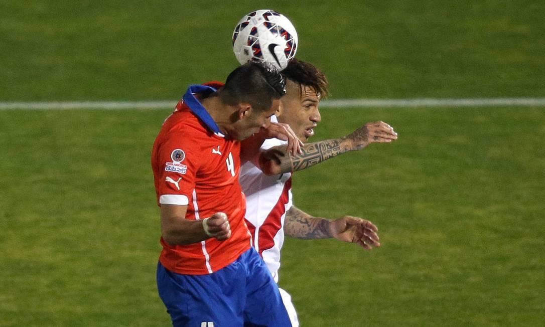 Chileno Isla e peruano Guerrero disputam a bola aérea em Santiago Jorge Saenz / AP