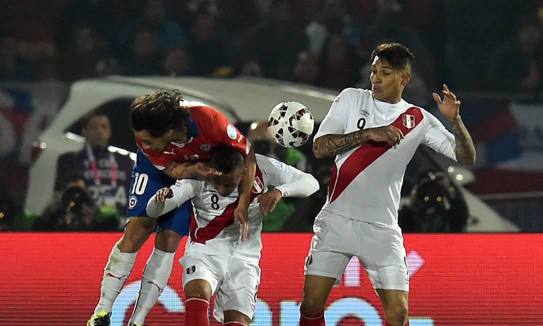 O chileno Valdivia divide a bola com os peruanos Cueva e Guerrero RODRIGO ARANGUA / AFP