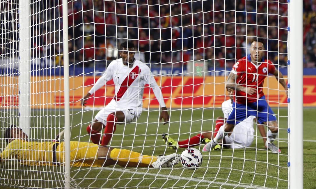 Enquanto o goleiro peruano Gallese se estica todo para evitar, o chileno Vargas observa a bola morrer no fundo da rede Andre Penner / AP