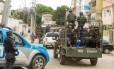 Observados por PMs, militares patrulham uma rua da Maré: Exército e Marinha deixam hoje definitivamente o complexo de favelas