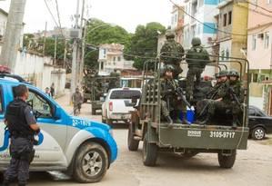 Observados por PMs, militares patrulham uma rua da Maré: Exército e Marinha deixam hoje definitivamente o complexo de favelas Foto: Antonio Scorza / Agência O Globo (01/04/2015)