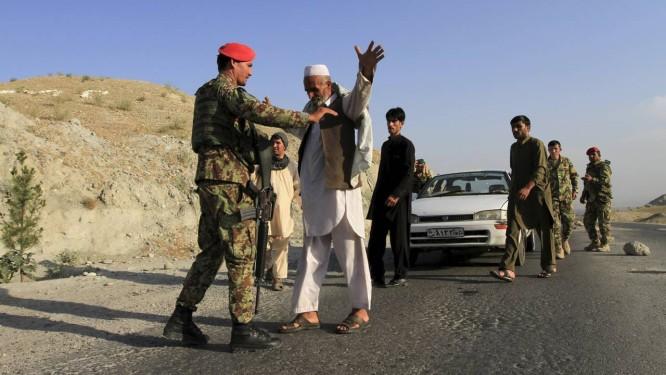 Medo. Soldados afegãos revistam pessoas na estrada rumo a Jalabad, capital da província de Nangarhar: EI teria tomado lugar do Talibã, decapitando seus líderes e atraindo jovens locais com dinheiro Foto: PARWIZ / REUTERS