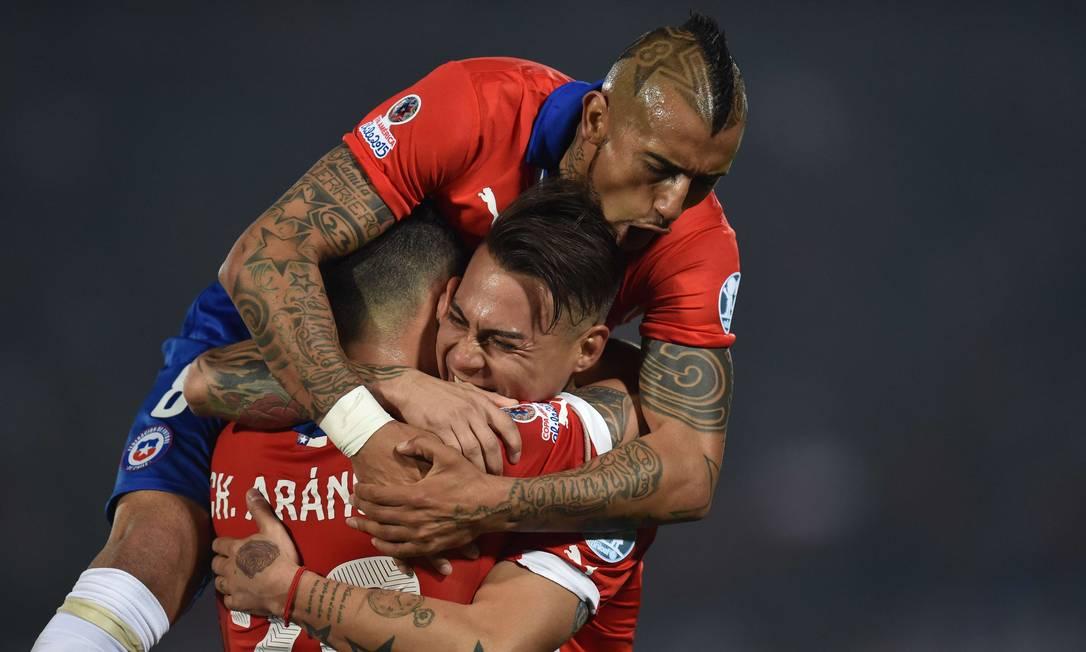 Vargas é abraçado por Aránguiz e Vidal ao fazer o segundo gol chileno RODRIGO ARANGUA / AFP