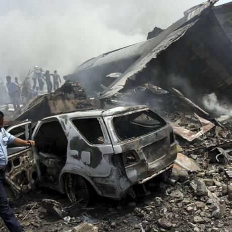 Bombeiros e forças de segurança tentam extinguir o fogo em torno dos destroços de avião militar indonésio Foto: Antara Foto / Reuters