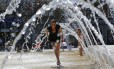 Britânica corre em chafariz de Nottingham. O serviço meteorológico inglês alertou sobre a possibilidade de ondas de calor com as maiores temperaturas do ano nesta terça e quarta-feiras