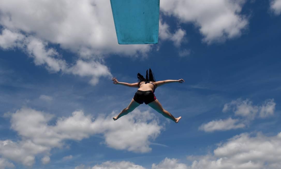 Mulher salta de plataforma em uma piscina pública de Neumuenster, na Alemanha, que tem temperatura em torno de 30ºC CARSTEN REHDER / AFP