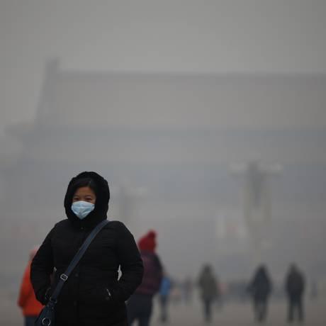 Mulher usa máscara para não respirar diretamente o ar poluído em Pequim Foto: KIM KYUNG-HOON / REUTERS