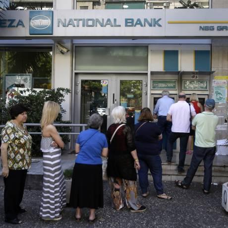 Clientes fazem fila em caixa eletrônico de banco grego Foto: Thanassis Stavrakis / AP