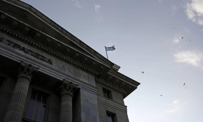 A bandeira grega tremula no topo do edifício do Banco Nacional da Grécia, em Thessaloniki Foto: Konstantinos Tsakalidis / Bloomberg