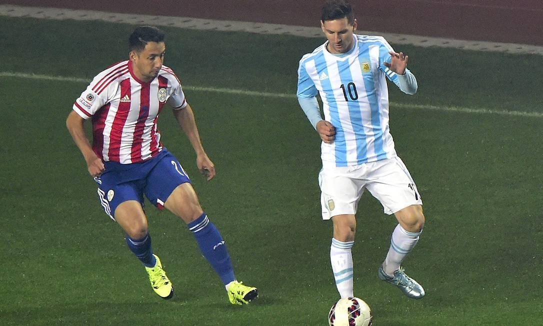 Argentino Lionel Messi recebe a marcação do zagueiro paraguaio Ivan Piris LUIS ACOSTA / AFP