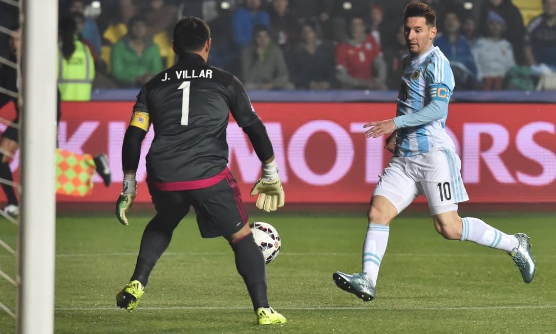Messi divide a bola com o goleiro paraguaio Villar NELSON ALMEIDA / AFP