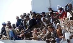 Imigrantes esperam para desembarcar do navio da Marinha italiana 'Chimera' no porto de Salerno, na Itália Foto: Francesco Pecoraro / AP