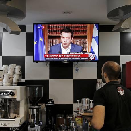 Garçom de cafeteria interrompe trabalho para ouvir o pronunciamento de Alexis Tsipras Foto: Christian Hartmann / Reuters