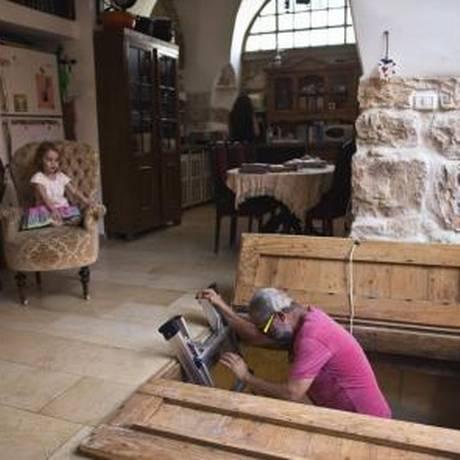 Tal, morador de Ein Karem, desce escada na sala de sua casa que leva a banheiro com 2000 anos de história descoberto durante reforma Foto: RONEN ZVULUN / REUTERS