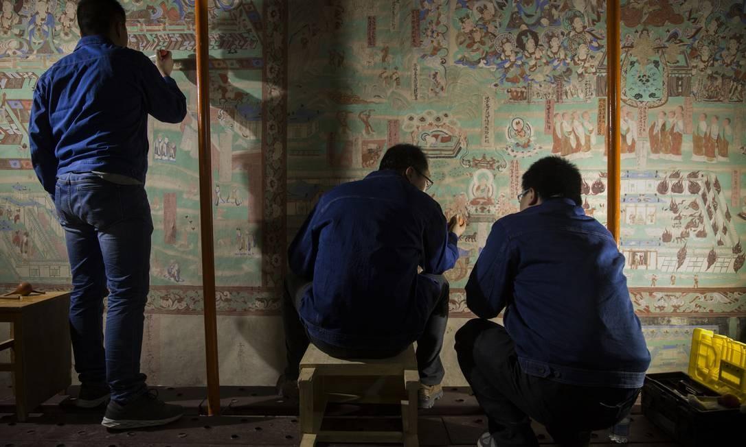 Trabalho de restauração em uma das 500 cavernas de Mogao, em Dunhuang, China: afrescos budistas Foto: ADAM DEAN/NYT