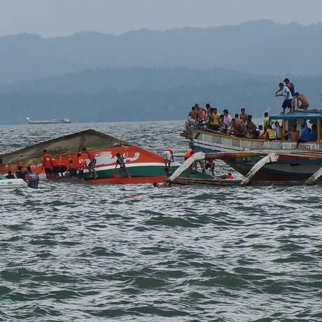 Equipes de resgate ajudam passageiros de balsa que naufragou nas Filipinas Foto: Ignatius Martin / AP