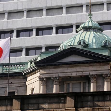 Bandeira do Japão tremula em frente ao BC do país, em Tóquio Foto: Yuriko Nakao/17-3-2015 / Bloomberg News