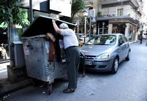 Cruzando a linha. Um idoso pega roupas encontradas em um baú para lixo Foto: Giannis Papanikos / Giannis Papanikos/AP