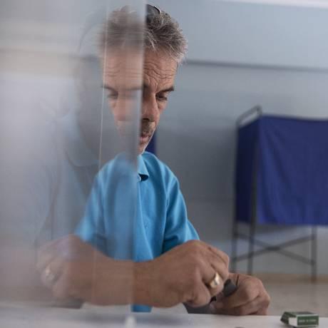 Funcionário do governo grego trabalha na preparação do referendo marcado para domingo. Urna pode ser vista ao fundo Foto: Petros Giannakouris / AP