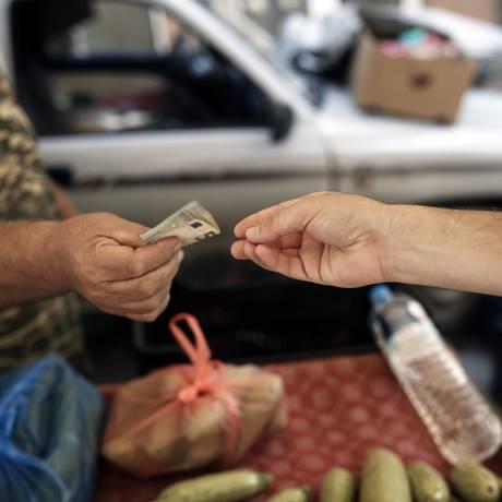 Vendedor recebe pagamento em dinheiro em feira em Tessalônica Foto: Konstantinos Tsakalidis / Bloomberg News