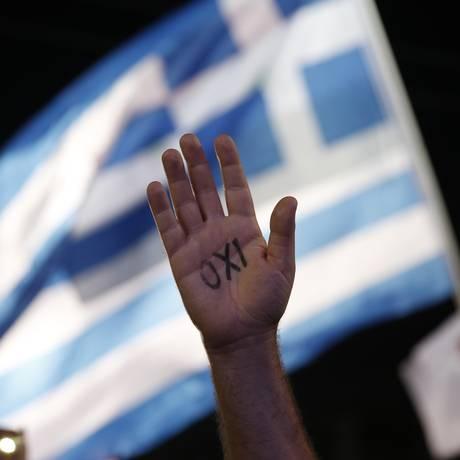 """Manifestante com palavra """"não"""" escrita na mão surge em frente à bandeira grega Foto: Petros Giannakouris / AP"""