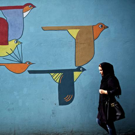 Mudanças. Iraniana passa por grafiti em muro de Teerã: fim das sanções ao governo melhoraria vida de cidadãos dentro e fora do país Foto: BEHROUZ MEHRI/AFP