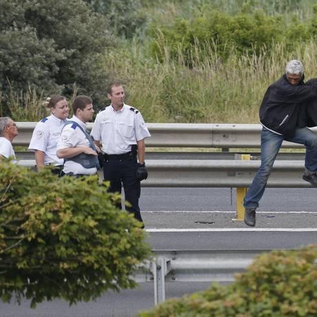 Policiais franceses ordenam a saída de um imigrante de um caminhão durante uma tentativa de fazer uma travessia clandestina para a Reino Unido pelo Eurotúnel Foto: VINCENT KESSLER / REUTERS