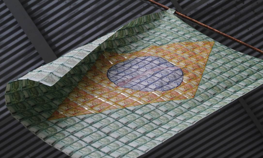 """Uma das obras do artista plástico pernambucano Lourival Cuquinha, a bandeira """"Amor, ordem e progresso"""" usa cédulas como suporte, em exibição em São Paulo, em 2013 Foto: / Ricardo Lima/Divulgação"""